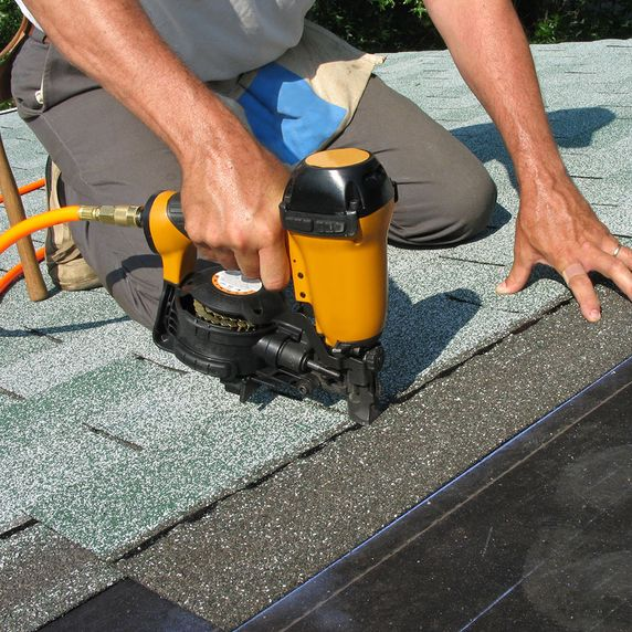 Roofer using a nail gun to repair a roof